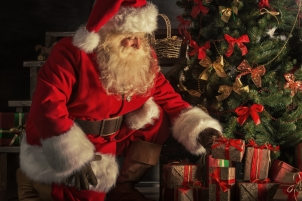 Santa is placing gift boxes under Christmas tree